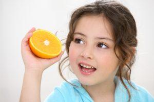 Criança segurando uma laranja para comer