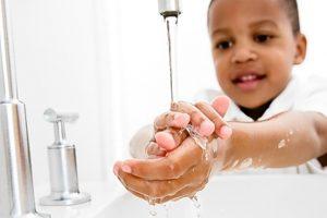 Criança lavando as mãos na pia
