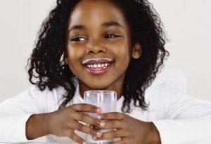 Criança tomando leite para prevenir a gripe