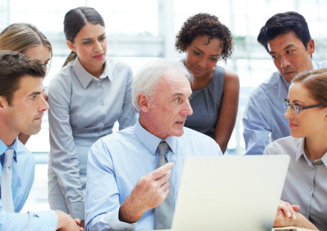 Funcionários reunidos em volta de uma mesa, discutindo assuntos pertinentes a empresa