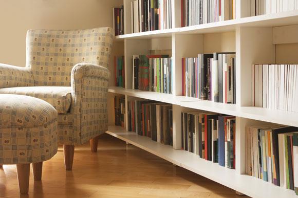 Sala com estante de livros e poltrona